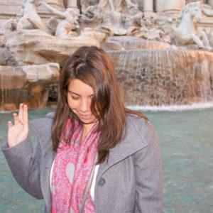 Woman throwing coin at Fontana di Trevi, Italy